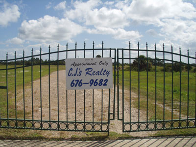 Gate to land sold by CJ's Realty, showing CJ's sign
